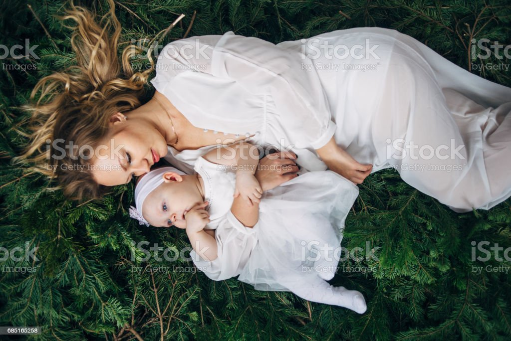 Mom and daughter are lying on Christmas trees royalty-free stock photo