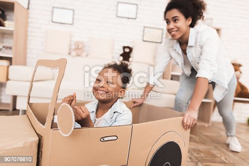 496487362 istock photo Mom and daughter are playing with big toy cars. 907076610