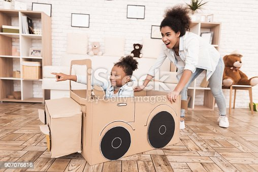 496487362 istock photo Mom and daughter are playing with big toy cars. 907076616