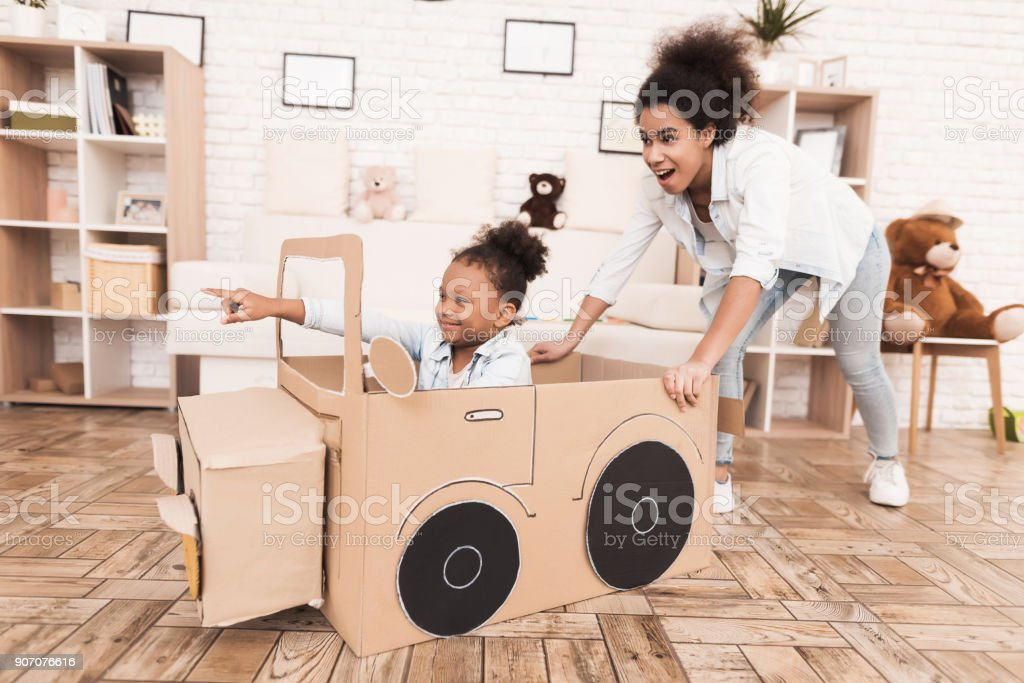 Mom and daughter are playing with big toy cars. stock photo