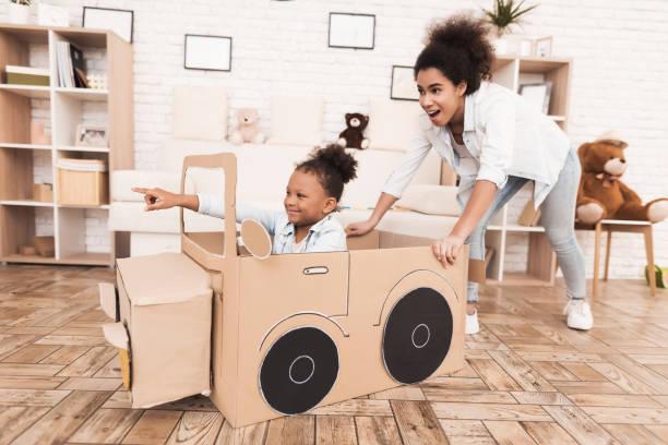 Mutter und Tochter spielen mit großen Spielzeugautos. – Foto