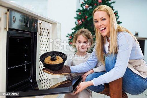 494086690istockphoto Mom and daughter are preparing  cake for Christmas - Kugelhupf 494085882