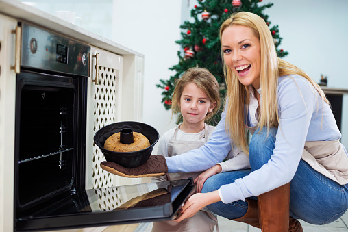 494086690 istock photo Mom and daughter are preparing  cake for Christmas - Kugelhupf 494085882