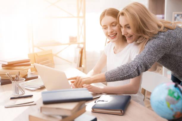 Mutter und Tochter sind etwas zusammen auf dem Laptop ansehen. – Foto