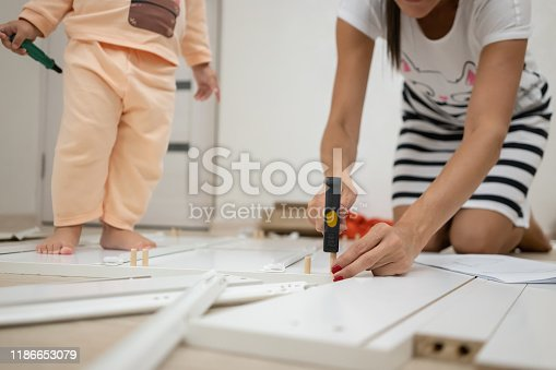 994789938 istock photo Mom and daughter collects a box. A woman is assembling a white wooden cabinet using a screwdriver 1186653079