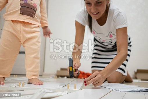 994789938 istock photo Mom and daughter collects a box. A woman is assembling a white wooden cabinet using a screwdriver 1186975009