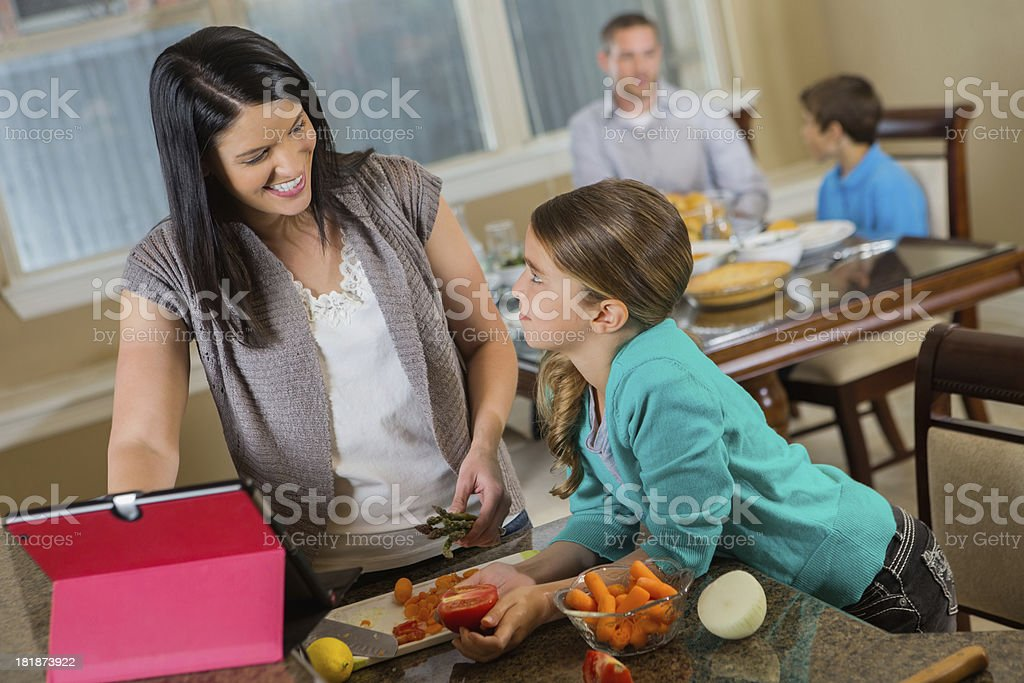 Mom and daughter cooking in family kitchen with digital tablet royalty-free stock photo