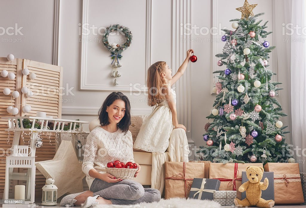 Mom and daughter decorate the Christmas tree. stock photo