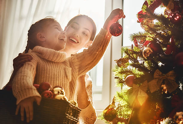 mom and daughter decorate the christmas tree - decorating stock photos and pictures