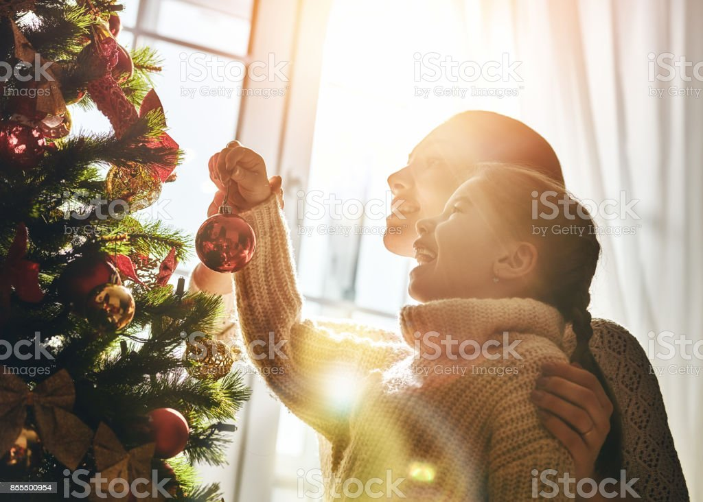 Mom and daughter decorate the Christmas tree stock photo