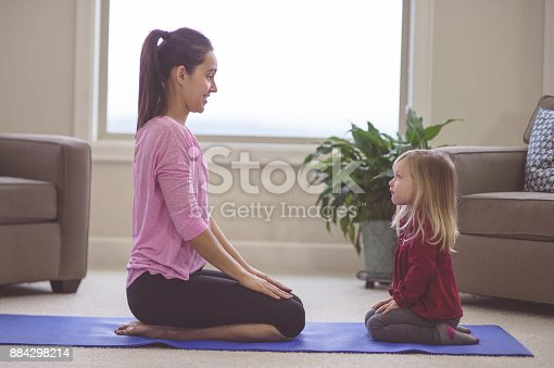 istock Mom and daughter do yoga together 884298214