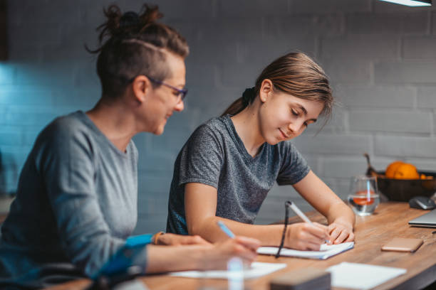 mom and daughter doing homework together at the kitchen table stock photo