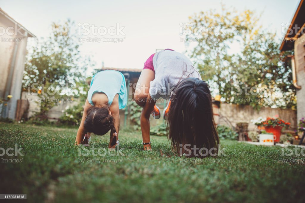Mom and daughter doing yoga outdoors Young woman and small child doing yoga in the back yard Adult Stock Photo