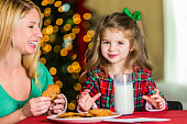 Playful mom and her daughter eat cookies that are left for Santa on Christmas Eve. A full glass of milk is on the table as well as a note for Santa. The mom laughs as the little girl smiles at the camera. Her mouth is full of cookies. They are both wearing pajamas. They have blond hair. The girl has a green ribbon in her hair. A Christmas tree is blurred in the background.