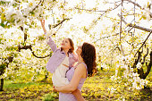 istock mom and daughter. family in purple clothe in blossoming spring garden. 1323788181