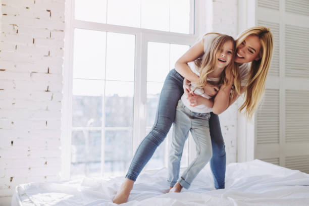 mom and daughter having fun at home - mother stock photos and pictures