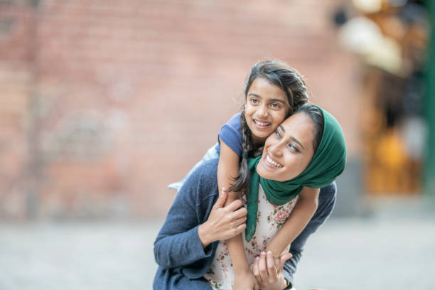 Mom And Daughter Having Fun A girl is riding on her mother's shoulders. The mother is wearing a hijab. religious veil stock pictures, royalty-free photos & images