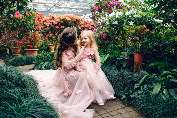 Mom and daughter in luxurious peach-colored dresses in a flowery garden stock photo