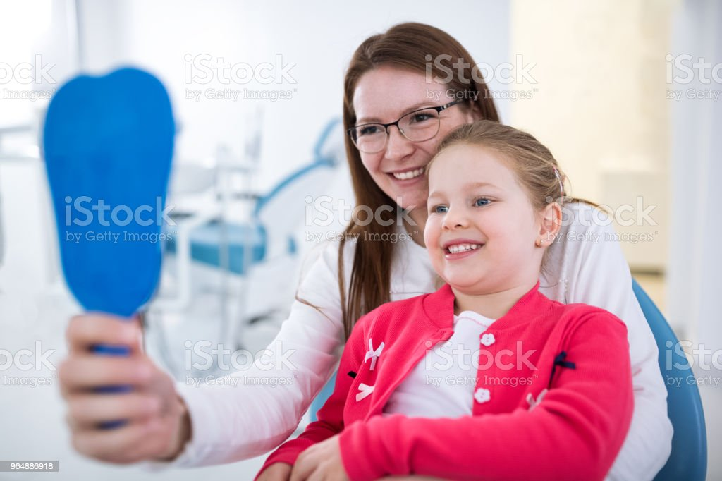 Mom and daughter looks teeth at mirror royalty-free stock photo