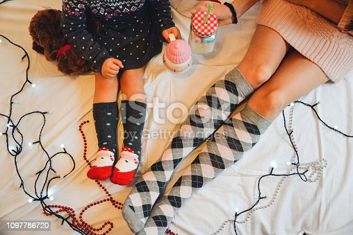 Woman relaxing at cozy home atmosphere, Mom and daughter lying on the bed in knitted socks, and drink hot milk with Homemade Marshmallows . Christmas socks and light, top view