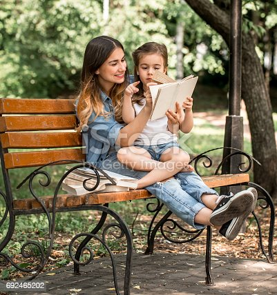 istock Mom and daughter on a bench reading a book 692465202
