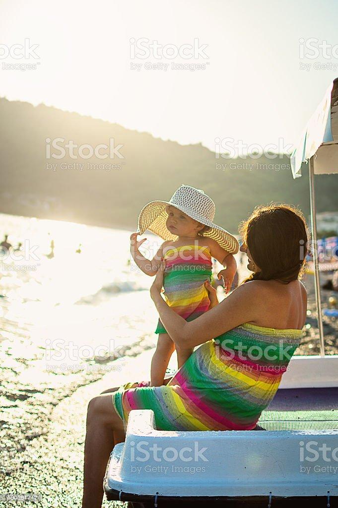 Mom and daughter on beach royaltyfri bildbanksbilder