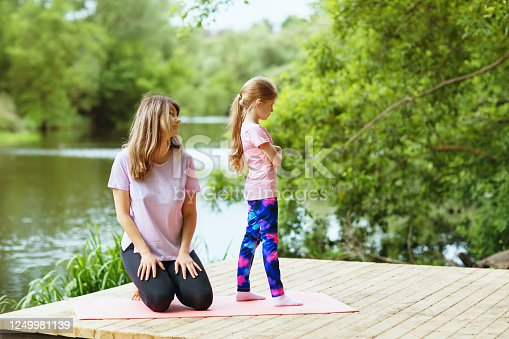 Mom and daughter on morning exercises in the park. The concept of reluctance to train