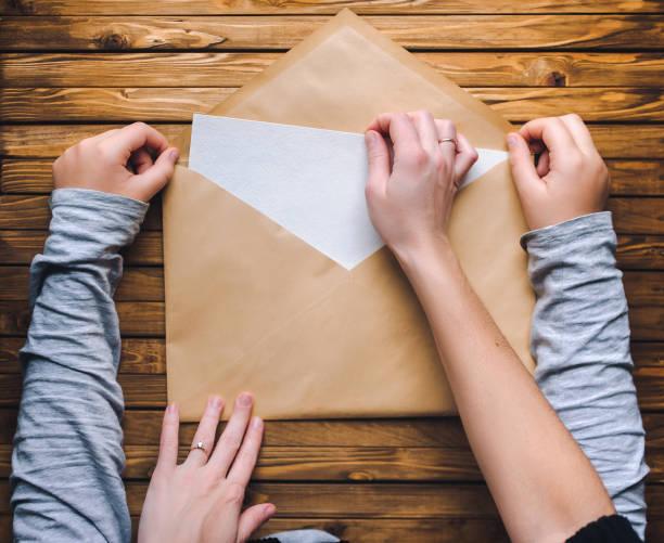 mutter und tochter einen großen braunen umschlag zu öffnen und nehmen sie einen brief oder ein sauberes weißes blatt papier. hölzerne hintergrund. - kinder verpackung stock-fotos und bilder