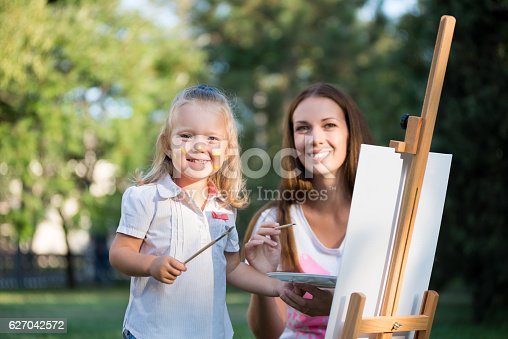 istock Mom and daughter paint colors in the park 627042572