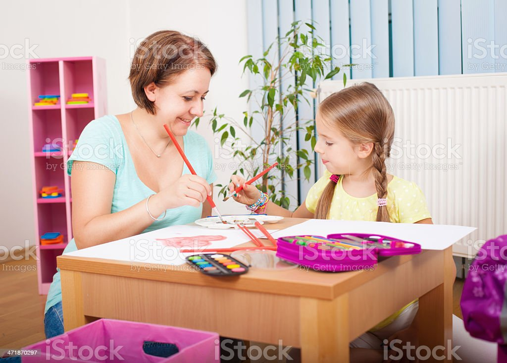 Mom and daughter painting stock photo