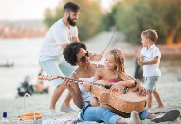 mutter und tochter spielen gitarre, und vater und sohn spielen fechten - kinder picknick spiele stock-fotos und bilder