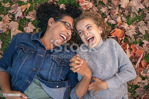 istock Mom and daughter playing in Autumn leaves 1218865388