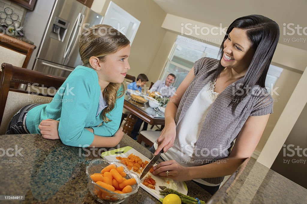 Mom and daughter preparing family dinner together in kitchen royalty-free stock photo