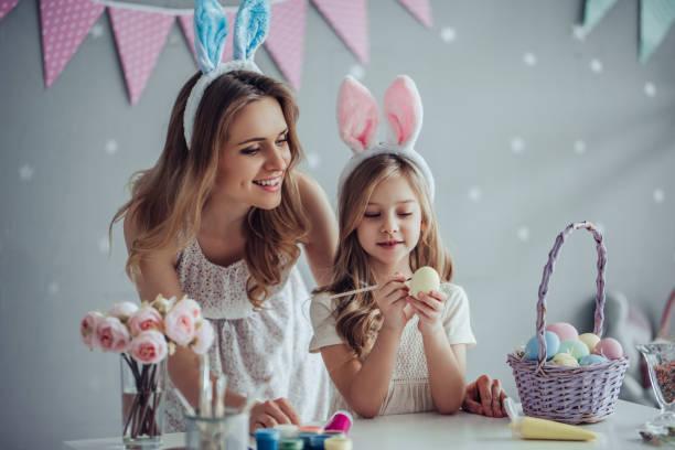 mom and daughter preparing for easter celebration - easter foto e immagini stock