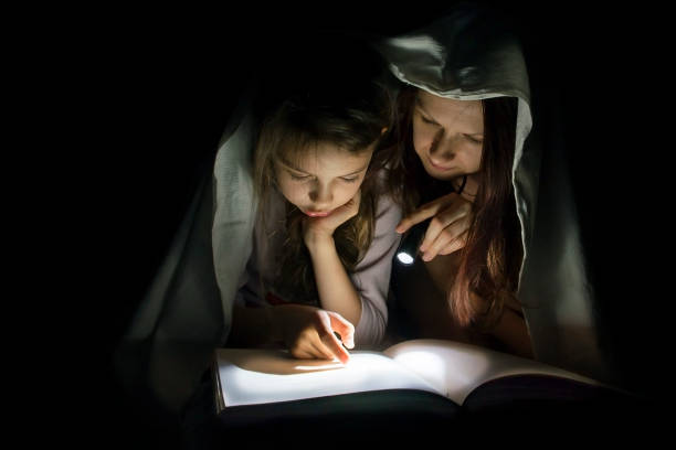 Mom and daughter read fairy tales in the dark under a blanket covering the book with a flashlight. stock photo