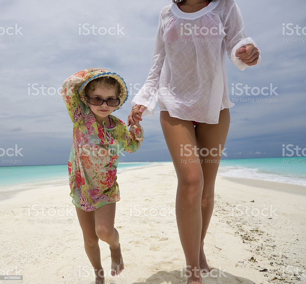 Mom and daughter running on sandbar royalty-free stock photo
