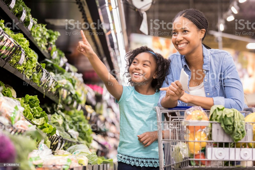 Mom and daughter shop for vegetables in supermarket stock photo
