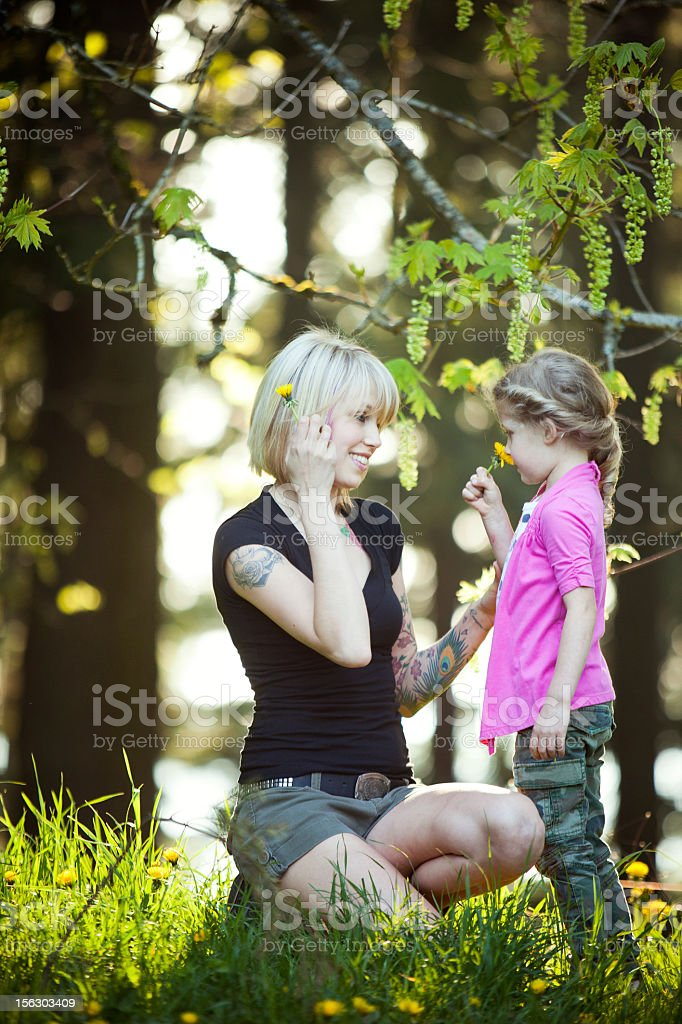 Mom and Daughter Smelling Flowers in Forest royalty-free stock photo