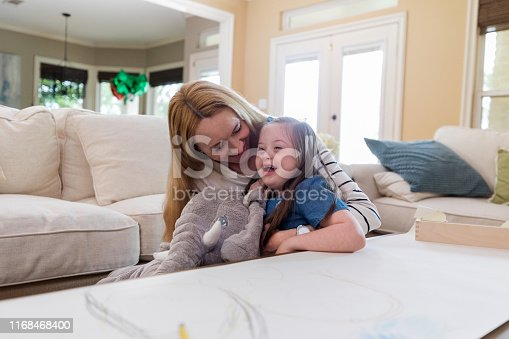 Loving mid adult mom and her adorable young daughter play at home together. The girl is holding a stuffed toy elephant.