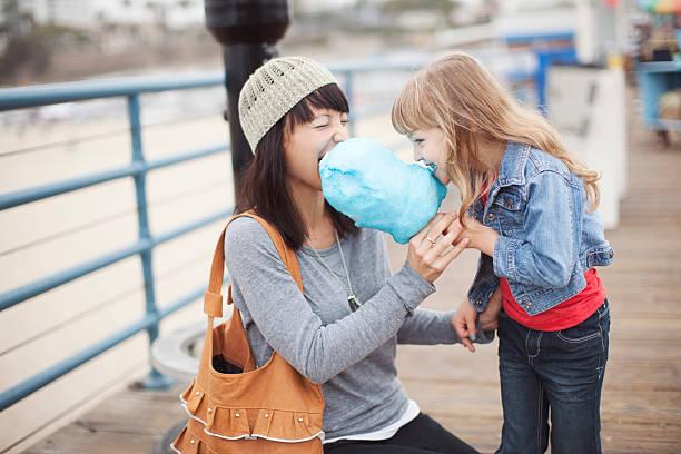 mutter und tochter einen bissen aus zuckerwatte - kinderhandtaschen stock-fotos und bilder