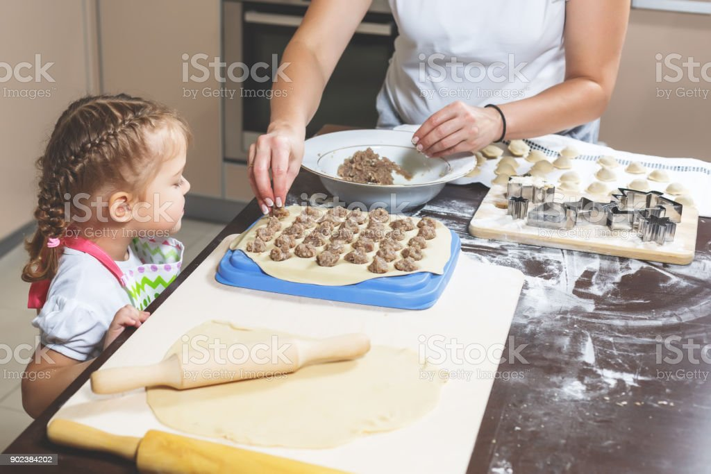 Mom and daughter together make dumplings in the kitchen stock photo