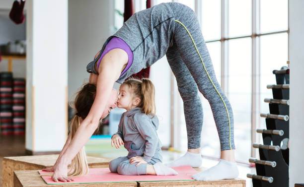 Mom and daughter together perform different exercises stock photo