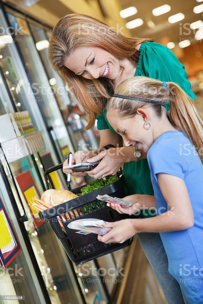 Mom and daughter using budget principles at the grocery store royalty-free stock photo
