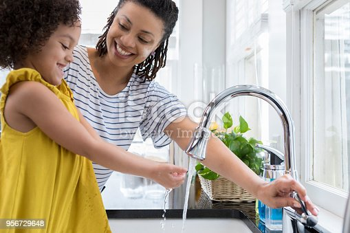 Mid adult mom turns water on in the kitchen sink. Her preschool age daughter is washing her hands.