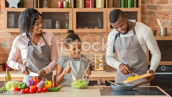 African mom and daughter watching dad while cooking together at home, panorama with copy space