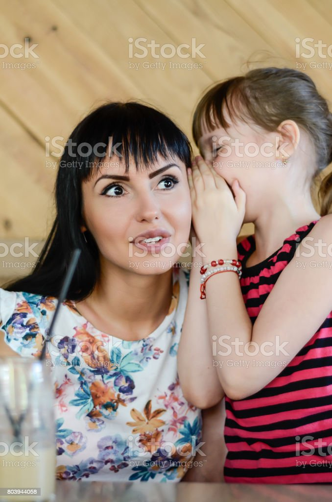 Mom and daughter whisper stock photo