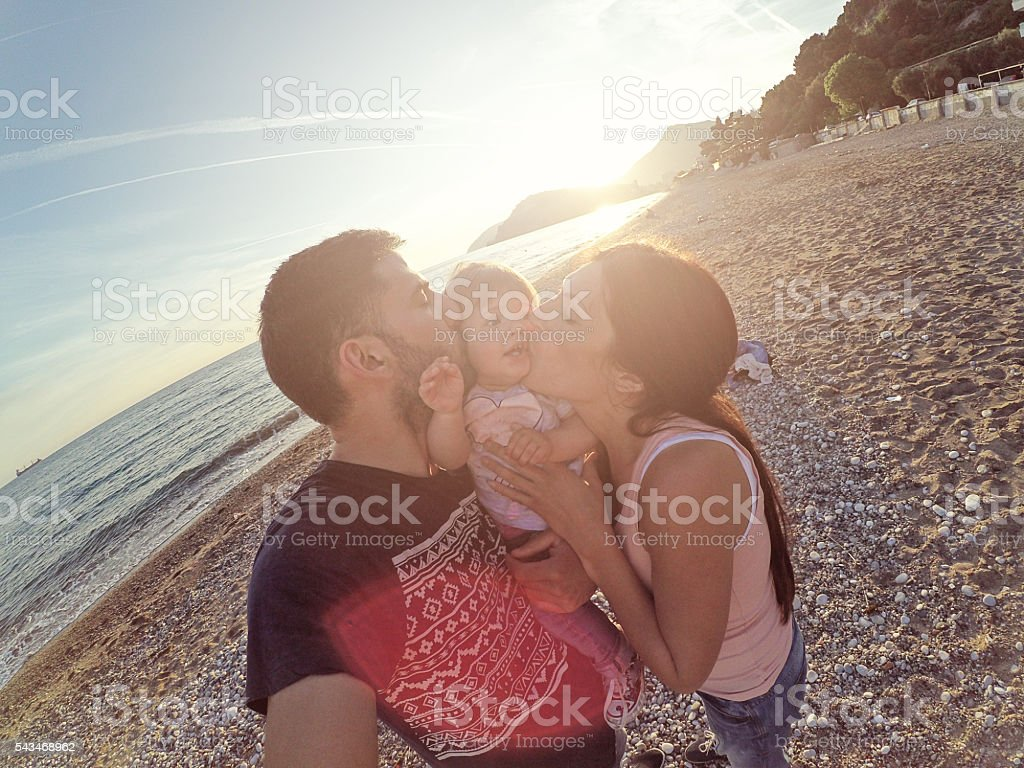 Mom and father kissing baby on beach selfie stock photo