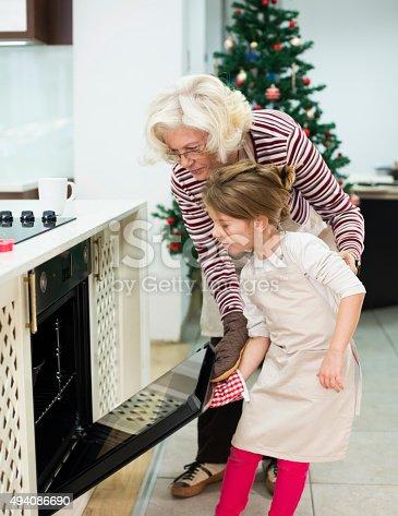 istock Mom and grandaughter are preparing  cake for Christmas - Kugelhupf 494086690