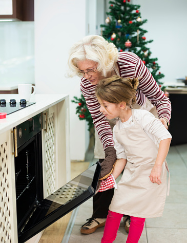 494086690 istock photo Mom and grandaughter are preparing  cake for Christmas - Kugelhupf 494086690
