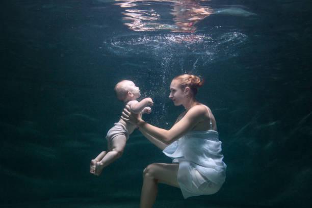 mama und ihr baby sind unter wasser. - frau tiefer ausschnitt stock-fotos und bilder